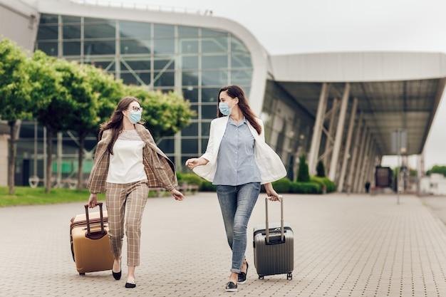 Duas mulheres felizes com máscaras protetoras após quarentena de coronavírus com malas vão para o aeroporto