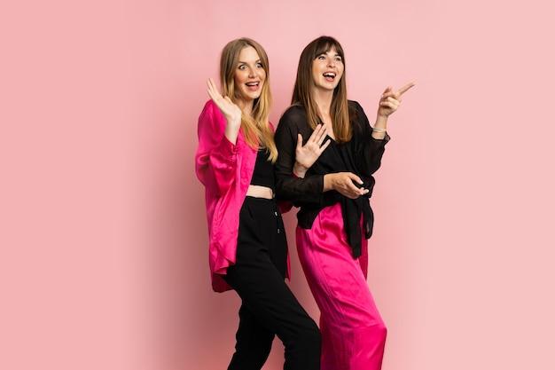 Duas mulheres felizes com roupas coloridas e elegantes, se divertindo na parede rosa