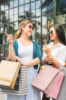 Duas mulheres felizes conversando e fazendo compras ao ar livre