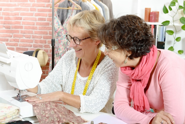 Duas mulheres felizes costurando em sua oficina