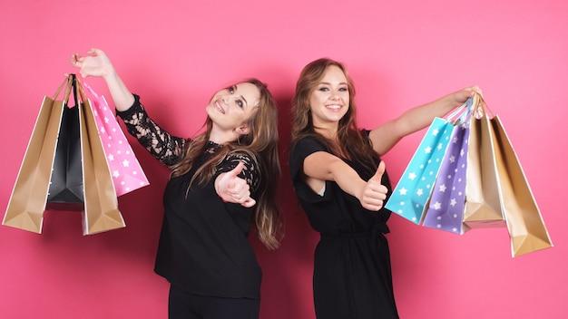 Duas mulheres felizes depois de fazer compras com um monte de pacotes sorrindo posar para a câmera