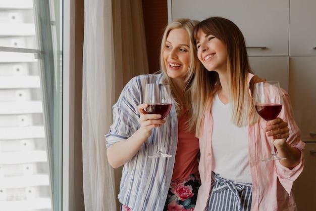 Duas mulheres felizes e despreocupadas, olhando para a janela e segurando um copo de vinho. atmosfera caseira acolhedora.