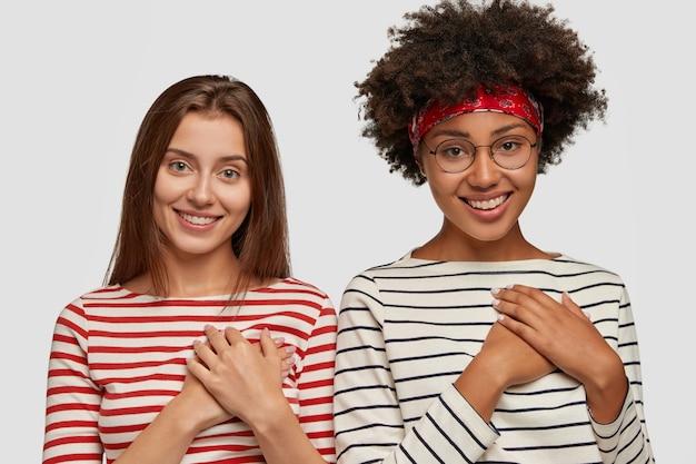 Duas mulheres felizes e multiétnicas de mãos dadas no peito, sorriem alegremente e relembram o grande momento, apreciam o apoio de alguém, agradecem, usam macacão listrado, isolado sobre parede branca