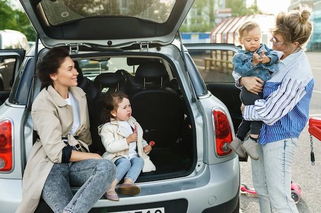 Duas mulheres felizes e seus lindos filhos ao lado de um carro em um estacionamento Foto Premium