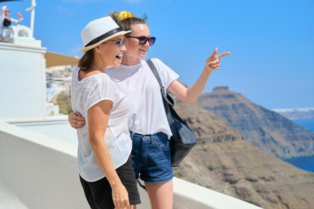 Duas mulheres felizes e sorridentes, mãe e filha adolescente viajando juntas, viagem de luxo em navio de cruzeiro para a famosa ilha grega de santorini