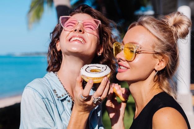 Duas mulheres felizes em forma de óculos de sol rosa e amarelo sorrindo, se divertindo, rindo com donuts, ao ar livre