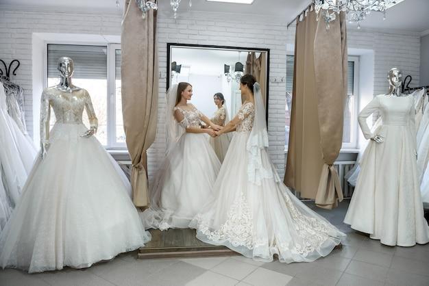 Duas mulheres felizes em vestidos de noiva posando no salão