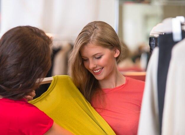 Duas mulheres felizes fazendo compras na loja de roupas