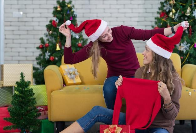Duas mulheres felizes, melhores amigas com batedor e chapéu de papai noel, animadas e surpresas abrindo uma caixa de presente na sala de estar de casa
