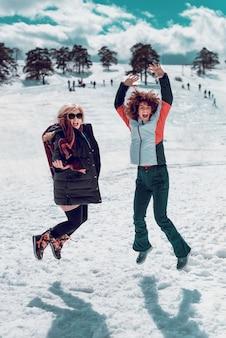Duas mulheres felizes pulando no ar e se divertindo na neve