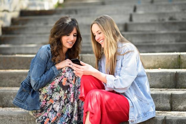 Duas mulheres felizes que compartilham de meios sociais com o telefone esperto que senta-se fora em etapas urbanas.