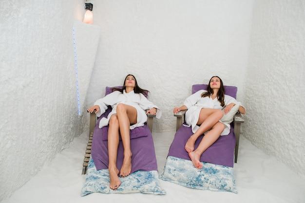 Duas mulheres felizes relaxantes em uma caverna de sal spa salarium