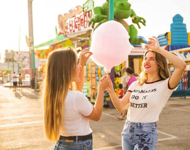 Duas mulheres felizes segurando algodão doce no parque de diversões