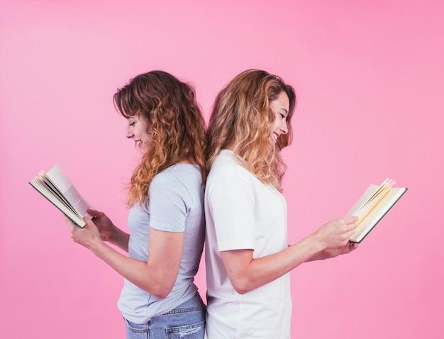 Duas mulheres, ficar, costas, costas, livro leitura, contra, fundo cor-de-rosa