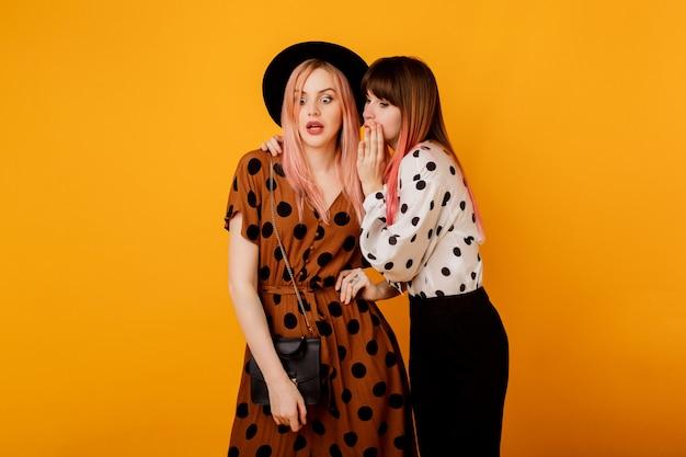 Duas mulheres fofocando sobre parede amarela em elegante roupa vintage