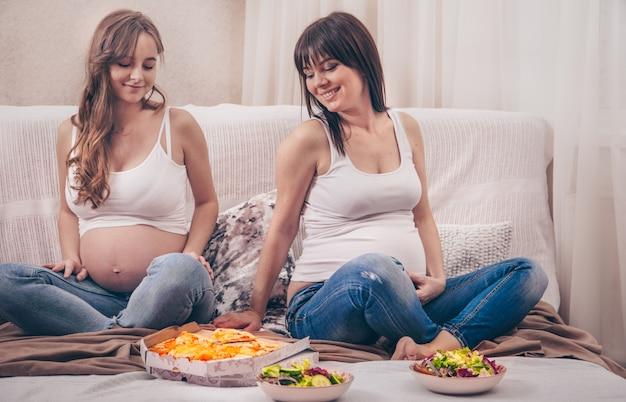 Duas mulheres grávidas comendo pizza e salada em casa