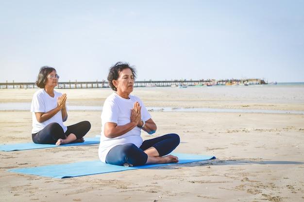 Duas mulheres idosas estão se exercitando na praia à beira-mar, fazendo yoga.
