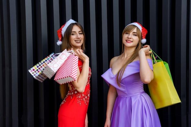 Duas mulheres incríveis com chapéu de papai noel e vestidos de noite elegantes segurando sacolas de compras