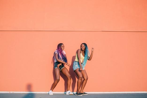 Duas mulheres irmãs ao ar livre ouvir música dança