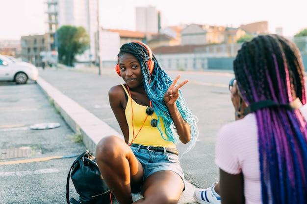 Duas mulheres irmãs ao ar livre, tirando foto fazendo sinal de vitória, ouvindo música