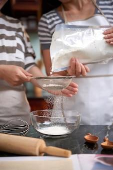 Duas mulheres irreconhecíveis derramando farinha na peneira na cozinha em casa