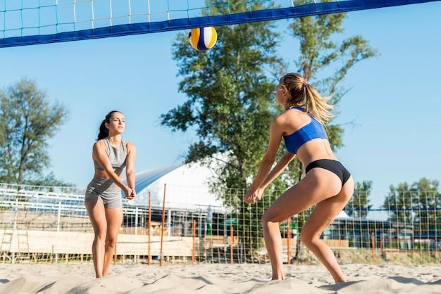 Duas mulheres jogando vôlei na praia juntas