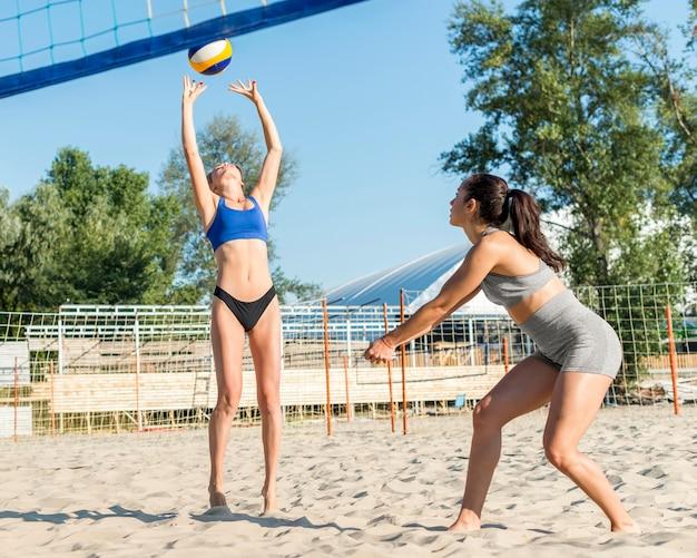 Duas mulheres jogando vôlei na praia