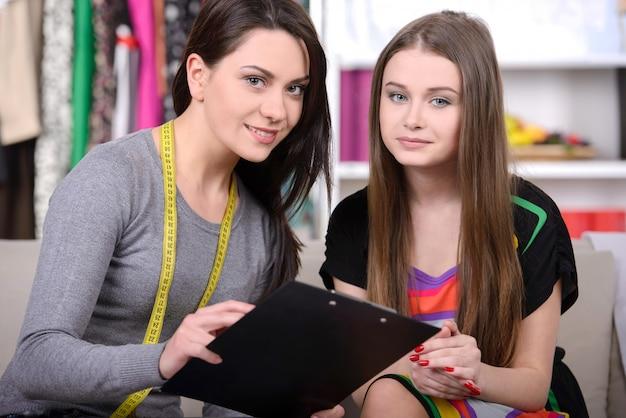 Duas mulheres jovens alegres, trabalhando no estúdio de design de moda