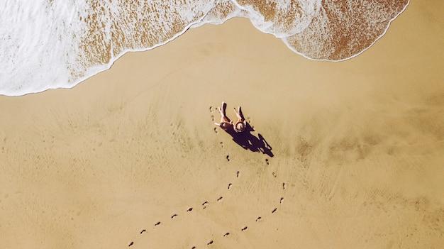 Duas mulheres, jovens amigas, pessoas na praia, vistas da vista superior vertical, aproveitam as férias de verão sentadas na areia para um banho de sol, ondas chegando e pegadas coloridas douradas para o feriado