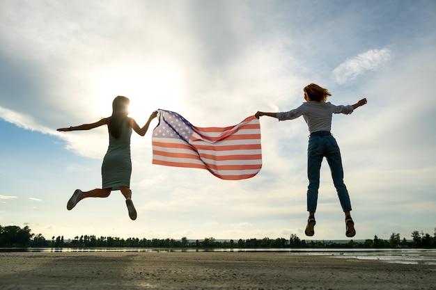 Duas mulheres jovens amigos segurando a bandeira nacional dos eua, pulando juntos ao ar livre ao pôr do sol. silhueta de meninas comemorando o dia da independência dos estados unidos. dia internacional do conceito de democracia.