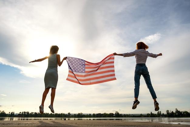 Duas mulheres jovens amigos segurando a bandeira nacional dos eua, pulando juntos ao ar livre ao pôr do sol. silhueta de meninas comemorando o dia da independência dos estados unidos.