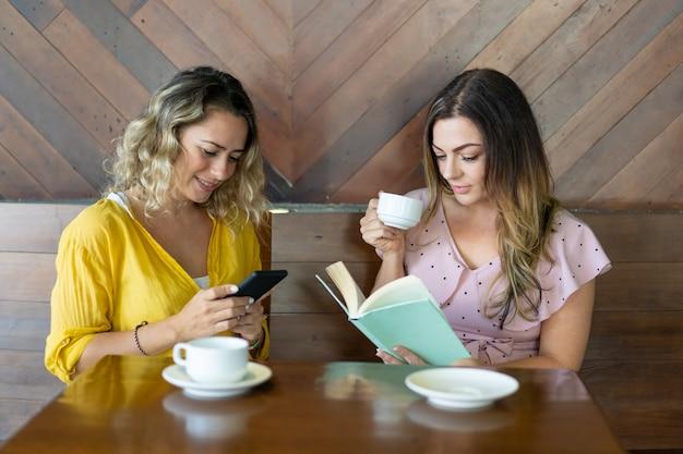 Duas mulheres jovens atraentes bebendo café e descansando no café