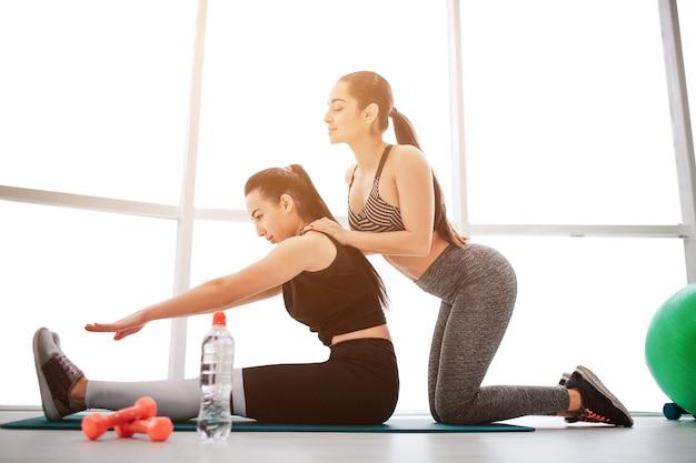 Duas mulheres jovens bem constituídas alongando-se
