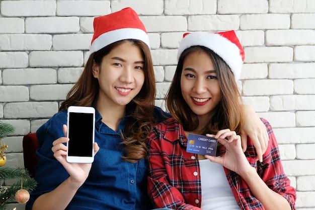 Duas mulheres jovens bonitos da ásia segurando o smartphone com tela em branco e cartão de crédito