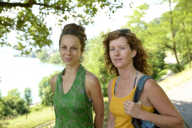 Duas mulheres jovens caminhando à beira do lago
