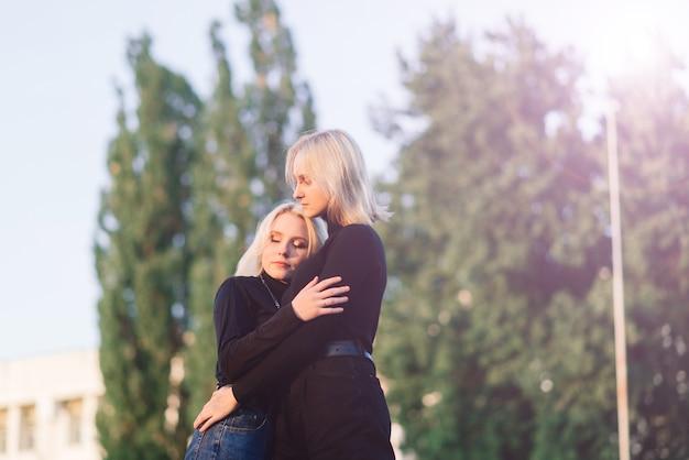 Duas mulheres jovens caminhando sorrindo se abraçando e se beijando ao ar livre na cidade