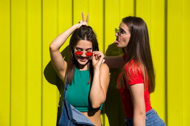 Duas mulheres jovens casuais bonitos brincando na frente da parede amarela