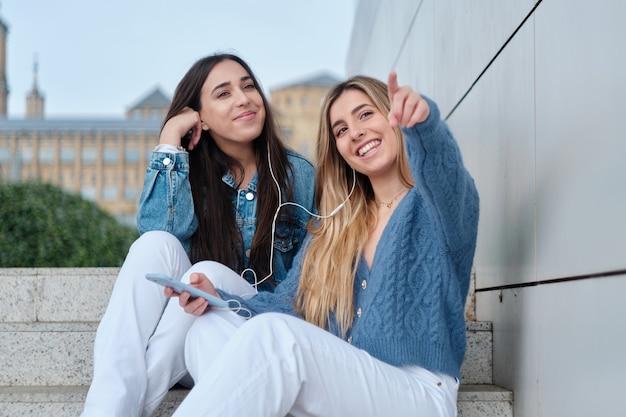 Duas mulheres jovens compartilhando fones de ouvido. eles olham na mesma direção. aponta o dedo. loira e morena. luz natural exterior.