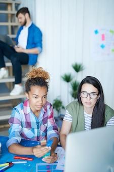 Duas mulheres jovens criativas trabalhando com computador