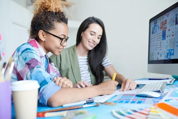 Duas mulheres jovens criativas trabalhando no escritório