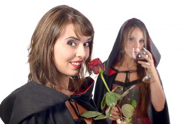 Duas mulheres jovens disfarçadas de halloween com um copo de sangue e uma rosa