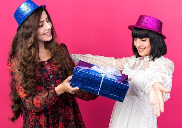 Duas mulheres jovens e alegres com chapéu de festa, uma olhando para a amiga, dando um pacote de presente, outra garota espalhando as mãos, olhando para um pacote isolado na parede rosa