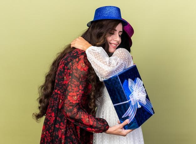 Duas mulheres jovens e amorosas com chapéu de festa se abraçando, uma segurando um pacote de presente, sorrindo com os olhos fechados, isolada na parede verde oliva