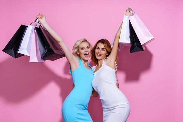 Duas mulheres jovens e atraentes em vestidos em pé perto uma da outra segurando sacolas de compras em rosa.