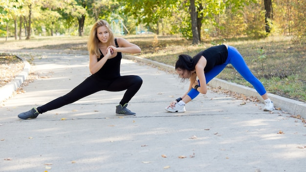 Duas mulheres jovens e atraentes malhando juntas em uma estrada do parque, fazendo exercícios de alongamento