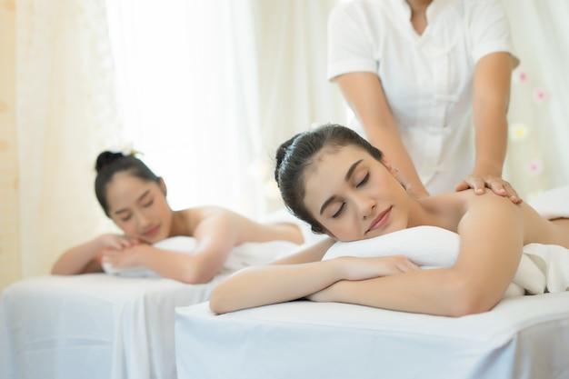 Duas mulheres jovens e bonitas relaxam durante a massagem no spa.
