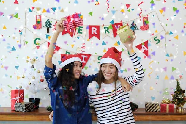 Duas mulheres jovens em chapéus de santa e segurando caixas de presente se divertindo com confetes coloridos na festa de natal.
