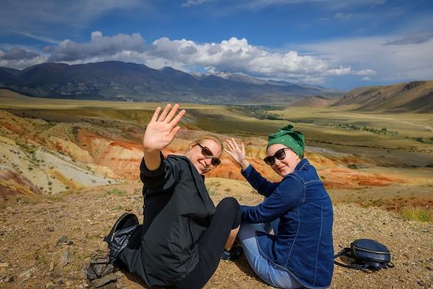 Duas mulheres jovens em óculos de sol na colina agitando os braços e sorrindo.