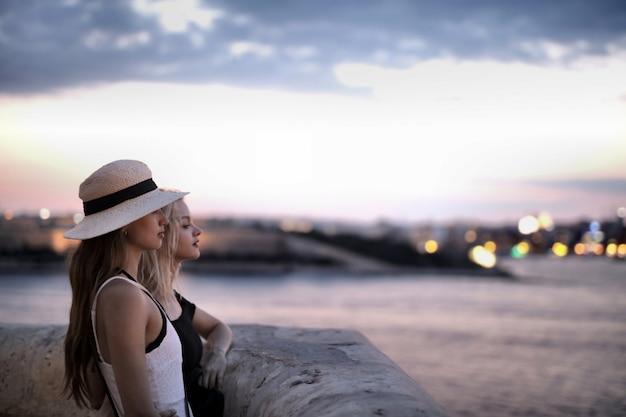 Duas mulheres jovens em pé perto da borda de pedra e olhando para o porto borrado