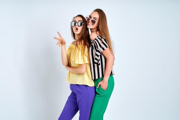 Duas mulheres jovens em roupas elegantes, moda, estúdio de beleza, tiro em fundo branco